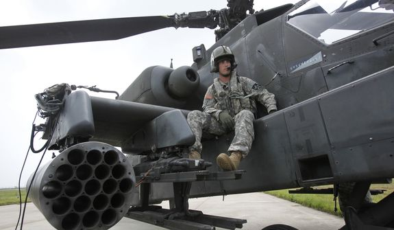 U.S. soldier Adam Elkins, chief warrant officer of 4th Aviation Attack Battalion 2nd Combat Aviation Brigade, sits on an AH-64D Apache attack helicopter as he waits for a live-fire drill at a U.S. air base in Gunsan, about 270 km (168 miles) south of Seoul, South Korea, Tuesday, July 21, 2009.  (AP Photo/Jo Yong-hak, Pool)