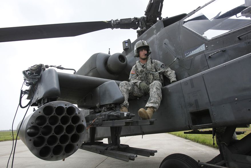 U.S. soldier Adam Elkins, chief warrant officer of 4th Aviation Attack Battalion 2nd Combat Aviation Brigade, sits on an AH-64D Apache attack helicopter as he waits for a live-fire drill at a U.S. air base in Gunsan, about 270 km (168 miles) south of Seoul, South Korea, Tuesday, July 21, 2009.  (AP Photo/Jo Yong-hak, Pool) ** FILE **