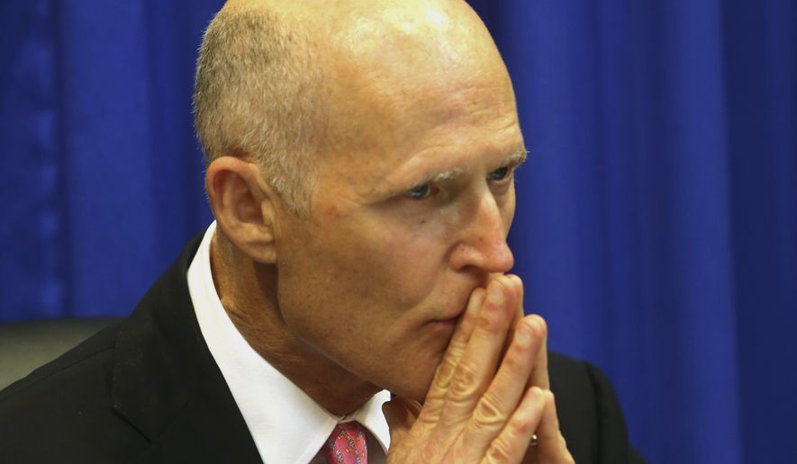 Florida Gov. Rick Scott listens to experts from public health, education and law enforcement about solutions on gun violence and Wednesday's shooting at Marjory Stoneman Douglas High School in Parkland, during a meeting at the state Capitol in Tallahassee, Fla., Tuesday, Feb. 20, 2018. (Scott Keeler/Tampa Bay Times via AP)
