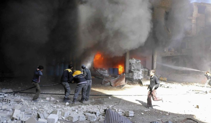 In this photo released on Tuesday Feb. 20, 2018, provided by the Syrian Civil Defense group known as the White Helmets, shows members of the Syrian Civil Defense extinguishing a store during airstrikes and shelling by Syrian government forces, in Ghouta, a suburb of Damascus, Syria. Intense Syrian government shelling and airstrikes of rebel-held Damascus suburbs killed at least 100 people since Monday in what was the deadliest day in the area in three years, a monitoring group and paramedics said Tuesday. (Syrian Civil Defense White Helmets via AP)