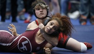 In this Friday, Feb. 16, 2018 photo, Euless Trinity's Mack Beggs, top, wrestles Lewisville's Elyse Nelson in the second round of the 110-pound girls division during the 6A Region II wrestling meet at Allen High School in Allen, Texas, Beggs, a senior from Euless Trinity High School near Dallas is transgender and in the process of transitioning from female to male. (Jae S. Lee/The Dallas Morning News via AP)