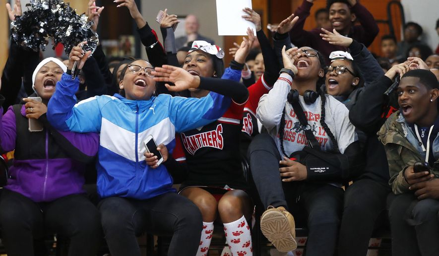 """In this Feb. 16, 2018, photo, University Prep Academy High School students react in Detroit to an announcement that all 600 students will see the film """"Black Panther."""" As the film debuts in theaters across the U.S., educators, philanthropist, celebrities, and business owners are pulling together their resources to bring children of color to see the film which features a black superhero in a fictional, un-colonized African nation. (AP Photo/Paul Sancya)"""