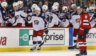 Columbus Blue Jackets defenseman Scott Harrington (4) celebrates his goal with teammates in front of New Jersey Devils defenseman Will Butcher (8) during the second period of an NHL hockey game, Tuesday, Feb. 20, 2018, in Newark, N.J. (AP Photo/Adam Hunger)