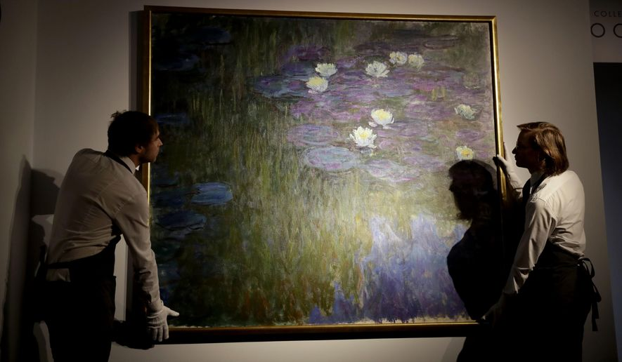 Christie's London auction house staff pose for photographs with Claude Monet's 'Nympheas en fleur', which will feature in the upcoming May 7-11 New York sale of the collection of Peggy and David Rockefeller, at their premises in London, Tuesday, Feb. 20, 2018. The Monet is estimated to fetch $50 million-$70 million (35.7 million to 50 million pounds, 40.5million to 56.7 million euro). The art collection amassed by billionaire David Rockefeller could raise more than $500 million for charity when it is auctioned this spring. (AP Photo/Matt Dunham)