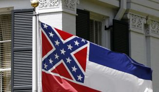 This Aug. 17, 2017, file photo shows the Mississippi state flag, top, sharing space with the bicentennial banner designed by the Mississippi Economic Council to recognize the state's bicentennial anniversary, outside the Governor's Mansion in Jackson, Miss.  AP Photo/Rogelio V. Solis, File) **FILE**