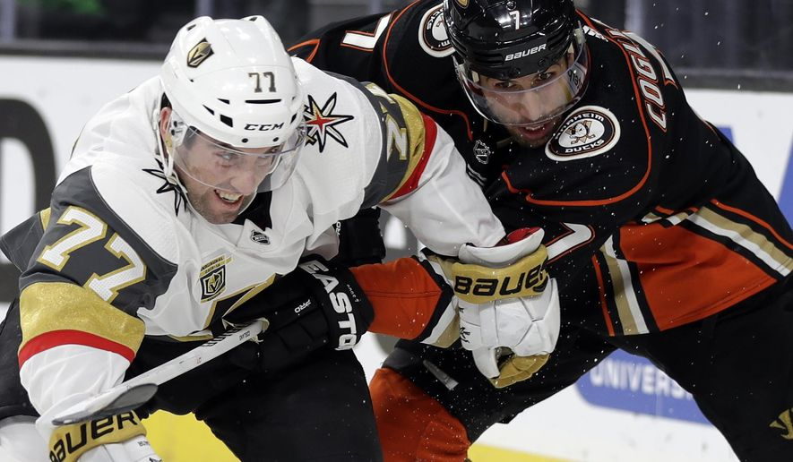 Vegas Golden Knights defenseman Brad Hunt, left, and Anaheim Ducks center Andrew Cogliano struggle for control of the puck during the first period of an NHL hockey game Monday, Feb. 19, 2018, in Las Vegas. (AP Photo/Isaac Brekken)