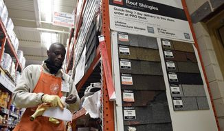 FILE - In this Feb. 23, 2015, file photo, Prince Addy of Manassas, Va., straightens up the shelves of roofing products at the Home Depot in Falls Church, Va. Home Depot a reports financial results Tuesday, Feb. 20, 2018. (AP Photo/Susan Walsh, File)
