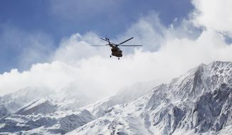 In this photo provided by Tasnim News Agency, a rescue helicopter flies over the Dena mountains while searching for wreckage of a plane that crashed on Sunday, in southern Iran, Monday, Feb. 19, 2018. Iranian search and rescue teams on Monday reached the site of a plane crash the previous day that authorities say killed all 65 people on board, Iran's Press TV reported.(Ali Khodaei/Tasnim News Agency via AP)