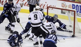 Los Angeles Kings' Torrey Mitchell (71) scores on Winnipeg Jets goaltender Connor Hellebuyck (37) during the third period of an NHL hockey game Tuesday, Feb. 20, 2018, in Winnipeg, Manitoba. (Trevor Hagan/The Canadian Press via AP)