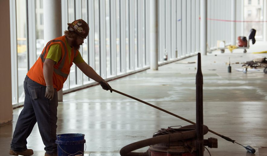 Christian Johnson with Rasure Flooring applies a moisture barrier on the second floor of the Indiana University School of Medicine-Evansville Thursday morning, Feb. 15, 2018. Construction continues as of Thursday, Feb. 15, 2018.  (Denny Simmons/Evansville Courier & Press via AP)