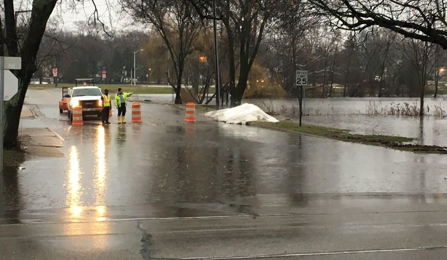 Workers block off a side road near Park Street in Kalamazoo Tuesday, Feb. 20, 2018 due to flooding.  Heavy rain and melting snow are combining to cause flooding and road closures in parts of Michigan's Lower Peninsula.(Meagan Beck/Kalamazoo Gazette-MLive Media Group via AP)