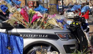 Flowers and signs adorn a Westerville Police car at a memorial outside the police department following a procession transporting the bodies of Westerville Police Officer Eric Joering and Anthony Morelli from the Franklin County Coroners Office to the Hill and Moreland funeral homes in Westerville, Ohio, Monday, Feb. 12, 2018. (Adam Cairns/The Columbus Dispatch via AP)