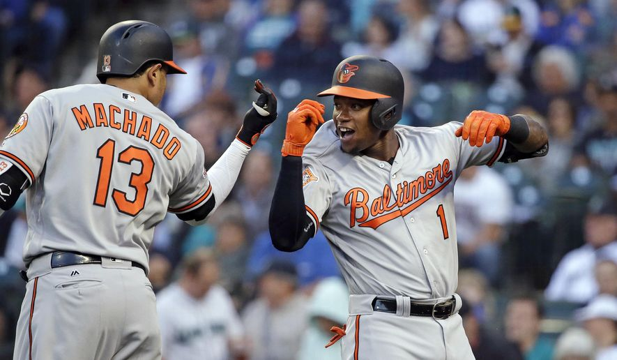 FILE - In this Aug. 14, 2017, file photo, Baltimore Orioles' Tim Beckham (1) is congratulated by Manny Machado on his home run against the Seattle Mariners on the first pitch of the first inning of a baseball game,in Seattle. Last year, Tim Beckham changed teams. This spring, he's trying a new position for the Baltimore Orioles, switching to third base from shortstop to accomodate teammate Manny Machado. (AP Photo/Elaine Thompson, File)