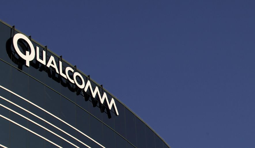 In this Nov. 2, 2011, file photo, a sign sits atop the Qualcomm headquarters building in San Diego. (AP Photo/Gregory Bull, File)