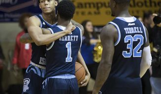 Rhode Island's Jeff Dowtin, left, celebrates the win with Jarvis Garrett, center, and Jared Terrell, right, after the second half of an NCAA college basketball game against La Salle, Tuesday, Feb. 20, 2018, in Philadelphia. Rhode Island won 95-93 in overtime. (AP Photo/Chris Szagola)