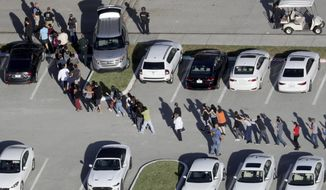 In this Feb. 14, 2018, file photo, students are evacuated by police from Marjory Stoneman Douglas High School in Parkland, Fla., after a shooter opened fire on the campus. (Mike Stocker/South Florida Sun-Sentinel via AP) ** FILE **
