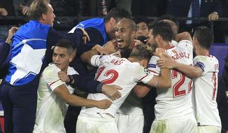 FILE - In this Nov. 21, 2017 file photo, Sevilla players celebrate after Guido Pizarro, center, scored their third goal during a Champions League group E soccer match between Sevilla and Liverpool, at the Ramon Sanchez Pizjuan stadium in Seville, Spain. Sevilla has won three in a row entering the first leg of a round of 16 Champions League match against Manchester United at home, on Wednesday Feb. 21, 2018 but coach Vincenzo Montella is far from happy with how his team has performed in attack. (AP Photo/Miguel Morenatti, File)