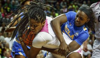 Oregon forward Ruthy Hebard, left, battles with UCLA forward Michaela Onyenwere for control of the ball during overtime of their Pac-12 NCAA college basketball game in Eugene, Ore., Monday, Feb. 19, 2018. Oregon won, 101-94 in overtime. (Andy Nelson/The Register-Guard via AP)