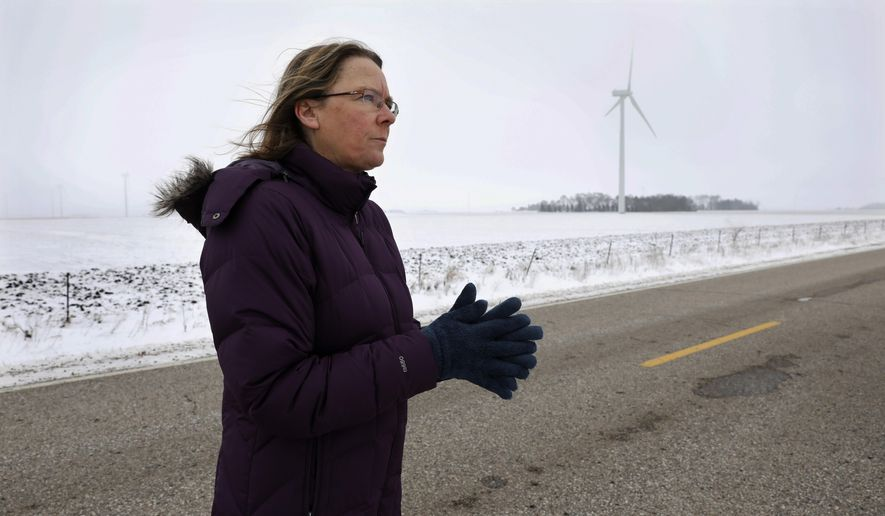 Dorenne Hansen, of Glenville, Minn., stands on a rural highway near a wind turbine in a field, Wednesday, Jan. 24, 2018, near Northwood, Iowa. Opponents of wind power are successfully stalling or rejecting wind-farm projects across the country. Criticism of wind turbines is nothing new, but this latest rebellion is raising a host of issues and halting developments. (AP Photo/Charlie Neibergall)