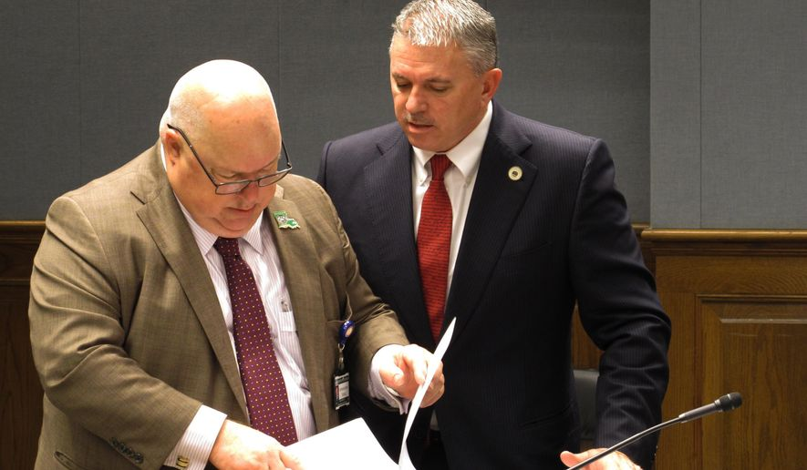 Agriculture Commissioner Mike Strain, left, speaks with Rep. Clay Schexnayder, R-Gonzales, about tax breaks that benefit the agriculture industry that Strain wants to preserve, on Tuesday, Feb. 20, 2018, in Baton Rouge, La. (AP Photo/Melinda Deslatte)