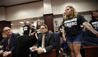 Lobbyists and attorneys listen as student survivors from last Wednesday's mass shooting at Marjory Stoneman Douglas High School interrupt a house legislative committee hearing in the hope to challenge lawmakers on gun control reform in Tallahassee, Fla., Wednesday, Feb. 21, 2018. (AP Photo/Gerald Herbert)
