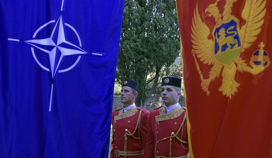 Montenegrin guards of honor stand between NATO, left, and Montenegro flags during ceremony to mark Montenegro's accession to NATO, in Podgorica, Montenegro, Wednesday, June 7, 2017. Despite opposition from Russia, Montenegro joined NATO on Monday after completing its membership formalities in Washington. (AP Photo/Risto Bozovic)