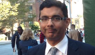 Dinesh D'Souza leaves federal court in New York, Tuesday, Sept. 23, 2014, after being sentenced to spend eight months in community confinement and undergo therapeutic counseling for arranging straw donors for a Senate candidate. D'Souza was spared from prison even though U.S. District Judge Richard M. Berman said the defendant continues to deflect responsibility and minimize his crime. (AP Photo/Larry Neumeister)