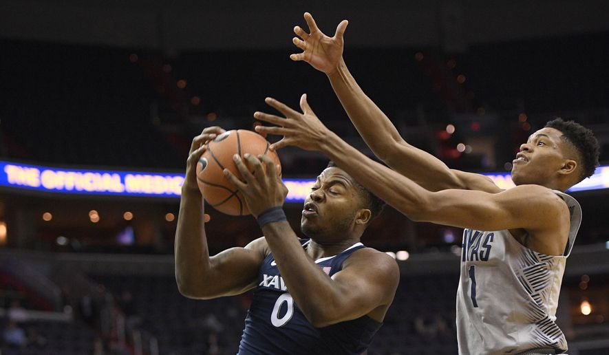 Xavier forward Tyrique Jones (0) grabs the ball against Georgetown forward Jamorko Pickett (1) during the first half of an NCAA college basketball game, Wednesday, Feb. 21, 2018, in Washington. (AP Photo/Nick Wass)