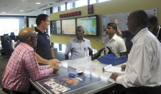 In this Monday, Feb. 19, 2018, photo, Australian search and rescue coordinator Rick Allen, second from left, trains foreign rescue officials in the Australian Maritime Safety Authority control room in Canberra, Australia. Officials from Mauritius, Maldives and Sri Lanka visited the authority's headquarters this week as part of a regional training program that began in 2015. (AP Photo/Rod McGuirk)