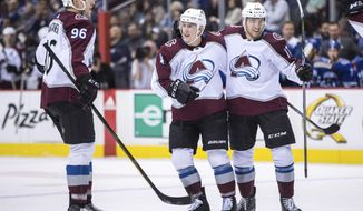 Colorado Avalanche's Mikko Rantanen, left, of Finland; Tyson Barrie, center; and Tyson Jost celebrate after Barrie scored the tying goal against the Vancouver Canucks during the third period of an NHL hockey game Tuesday, Feb. 20, 2018, in Vancouver, British Columbia. (Darryl Dyck/The Canadian Press via AP)