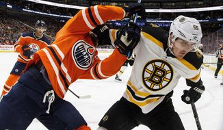 Boston Bruins' Nick Holden (55) and Edmonton Oilers' Adam Larsson (6) battle in the corner during the third period of an NHL hockey game Tuesday, Feb. 20, 2018, in Edmonton, Alberta. (Jason Franson/The Canadian Press via AP)
