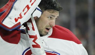 After going down hard on the ice Montreal Canadiens goalie Carey Price takes off his face mask and waits for the team trainer during the second period of an NHL hockey game Tuesday, Feb. 20, 2018 in Philadelphia. The Flyers won 3-2. (AP Photo/Tom Mihalek)