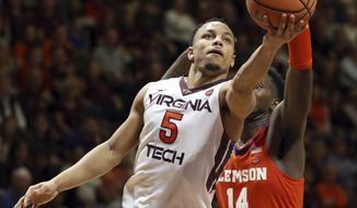 Virginia Tech's Justin Robinson (5) scores past Clemson's Elijah Thomas (14) during the first half of an NCAA college basketball game in Blacksburg Va., Wednesday, Feb. 21, 2018. (Matt Gentry/The Roanoke Times via AP)