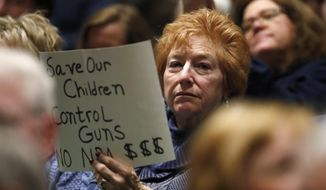 A protester waves a sign as U.S. Rep. Mike Coffman, R-Colorado, talks during a town hall meeting with constituents in a high school assembly hall Tuesday, Feb. 20, 2018, in Greenwood Village, Colo. Coffman was peppered with questions about gun control in the wake of the mass shooting at a school in south Florida last week. (AP Photo/David Zalubowski)
