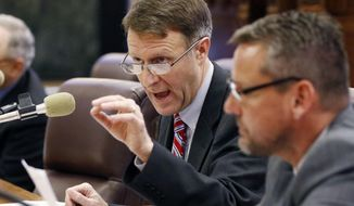 Senate Education Committee chairman Gray Tollison, R-Oxford, center, explains to committee members what each handout contains as they discuss the House's version of an education bill during a committee meeting at the Capitol in Jackson, Miss., Wednesday, Feb. 21, 2018. Legislators are considering rewriting the Mississippi Adequate Education Program. (AP Photo/Rogelio V. Solis)