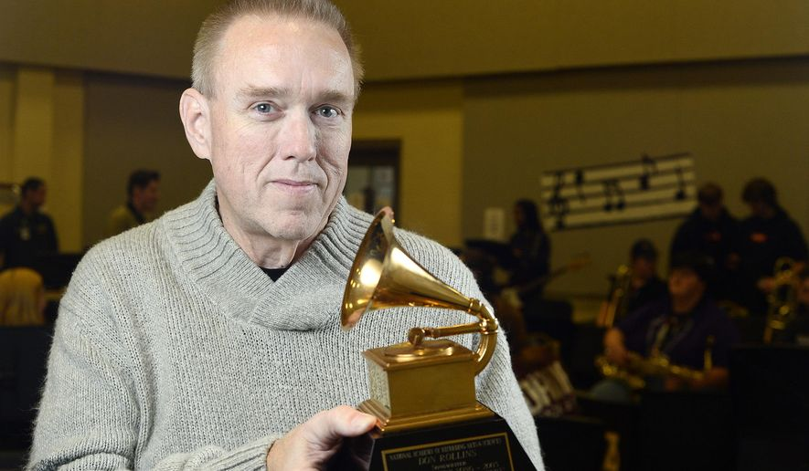 """In this Thursday, Feb. 8, 2018, photo, Don Rollins poses for a photo holding his Grammy Award for Best Country Song of 2003 at Vidor High School in Vidor, Texas. The Vidor native, who won the award for co-writing """"It's Five O'Clock Somewhere"""" for Alan Jackson and Jimmy Buffett, returned in 2014 to his hometown and high school, where he runs the program that first got him hooked on music. (Ryan Pelham/The Beaumont Enterprise via AP)"""