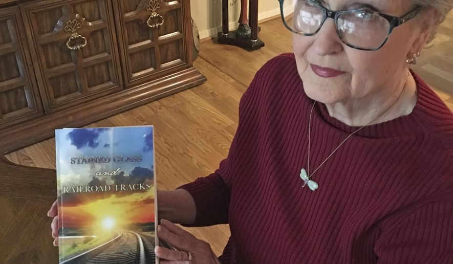 """In this Feb. 12, 2018 photo, Virginia Pirtle Malicoat displays the book she wrote about her hometown, the ghost town Phillips, titled """"Stained Glass and Railroad Tracks."""" (Jon Mark Beilue/Amarillo Globe-News via AP)"""