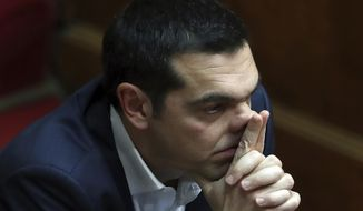 Prime Minister Alexis Tsipras attends a parliament session in Athens, Wednesday, Feb. 21, 2018. In a heated debate set to last more than 14 hours, Greek lawmakers were to decide on whether to launch an investigation into 10 senior politicians, including two former prime ministers, over allegations they were involved in a pharmaceutical bribery scandal. (AP Photo/Thanassis Stavrakis)