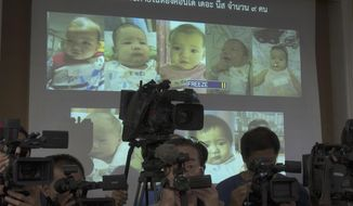 FILE - In this Aug. 12, 2014, file photo, the media attend a press briefing where Thai police display projected pictures of surrogate babies born to a Japanese man who is at the center of a surrogacy scandal during a press conference at the police headquarters in Chonburi, Thailand. The Japanese father of the surrogate babies Mitsutoki Shigeta is the son of the founder of Japanese telecom and insurance company Hikari Tsushin and earns millions of dollars a year in dividends. (AP Photo/Sakchai Lalit, File)
