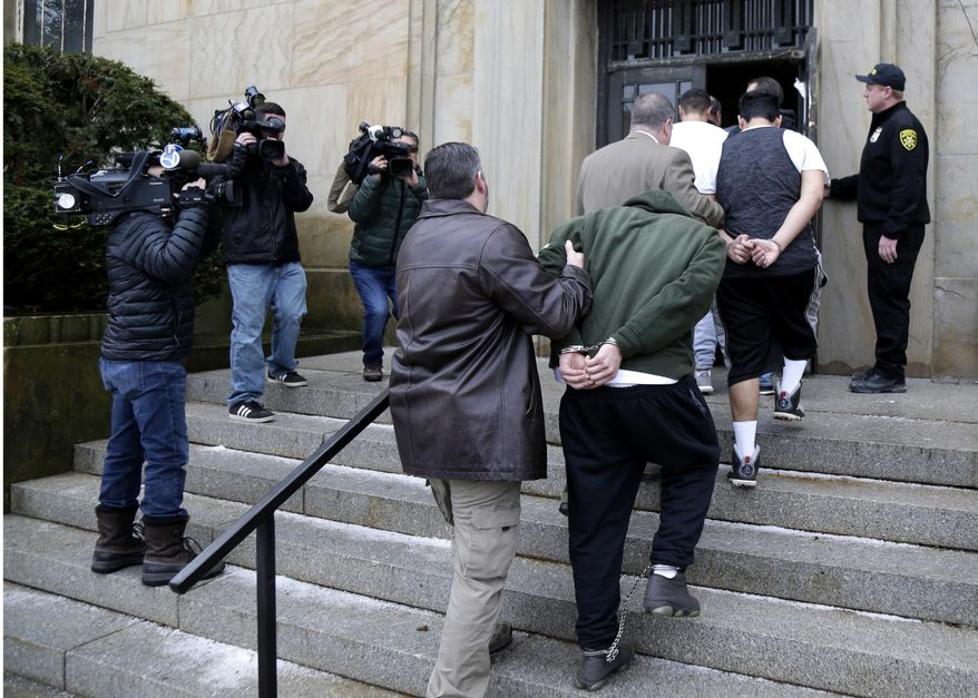 In this Jan. 11, 2018, file photo, suspected members of the MS-13 gang are escorted to their arraignment in Mineola, N.Y. A sweep of alleged MS-13 gang members on Long Island has racked up impressive arrest totals but also left unanswered questions. Since May, federal authorities say they've arrested more than 220 members of the notorious street gang. But authorities have largely declined multiple requests by for even the most basic information about the arrests. (AP Photo/Seth Wenig, File)