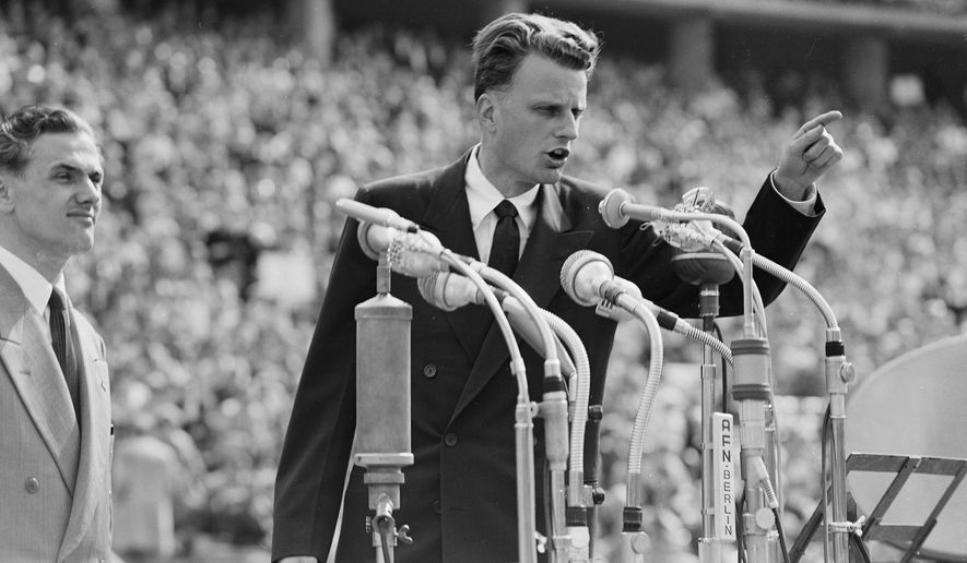 FILE - In this June 27, 1954 file photo, Evangelist Billy Graham speaks to over 100,000 Berliners at the Olympic Stadium in Berlin, Germany.   Graham, who transformed American religious life through his preaching and activism, becoming a counselor to presidents and the most widely heard Christian evangelist in history, has died. Spokesman Mark DeMoss says Graham, who long suffered from cancer, pneumonia and other ailments, died at his home in North Carolina on Wednesday, Feb. 21, 2018. He was 99. (AP Photo, File)
