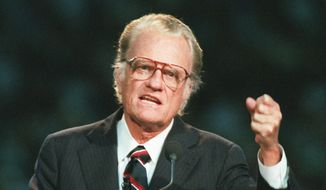 In this Oct 26, 1994, file photo, Evangelist Billy Graham begins his sermon in Atlanta's Georgia Dome. Graham, who transformed American religious life through his preaching and activism, becoming a counselor to presidents and the most widely heard Christian evangelist in history, has died. Spokesman Mark DeMoss says Graham, who long suffered from cancer, pneumonia and other ailments, died at his home in North Carolina on Wednesday, Feb. 21, 2018. He was 99. (AP Photo/John Bazemore, File)