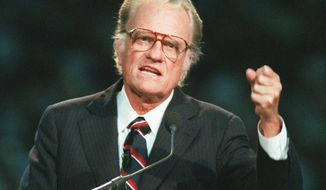 In this Oct 26, 1994 photo, Evangelist Billy Graham begins his sermon in Atlanta's Georgia Dome. Graham, who transformed American religious life through his preaching and activism, becoming a counselor to presidents and the most widely heard Christian evangelist in history, has died. Spokesman Mark DeMoss says Graham, who long suffered from cancer, pneumonia and other ailments, died at his home in North Carolina on Wednesday, Feb. 21, 2018. He was 99. (AP Photo/John Bazemore, File)