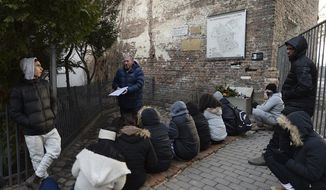 """A group of college students from Israel being taught about Holocaust history at a fragment of the wall that isolated the Warsaw Ghetto and that a regional official wants to put on a list of protected historical monuments, in Warsaw, Poland, Tuesday, Feb. 20, 2018. The wall was built in 1940, when the Nazi Germans closed the area of Warsaw they called the """"Jewish district."""" (AP Photo/Czarek Sokolowski)"""