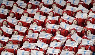 North Korea supporters sing and wave flags ahead of the pairs free skate figure skating final in the Gangneung Ice Arena at the 2018 Winter Olympics in Gangneung, South Korea, Thursday, Feb. 15, 2018. (AP Photo/Bernat Armangue, File)