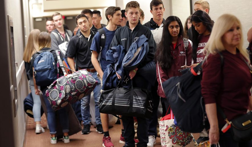 Student survivors from Marjory Stoneman Douglas High School, scene of a deadly mass shooting last Wednesday, prepare to load their bags on busses, after spending the night in the civic center in Tallahassee, Fla., Wednesday, Feb. 21, 2018. Several busloads of survivors marched from the civic center to the state capitol to pressure lawmakers on gun control reform. (AP Photo/Gerald Herbert)