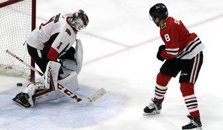 Chicago Blackhawks center Nick Schmaltz, right, scores against Ottawa Senators goalie Mike Condon in the shootout of an NHL hockey game Wednesday, Feb. 21, 2018, in Chicago. The Blackhawks won 3-2. (AP Photo/Nam Y. Huh)