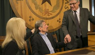 Kent Whitaker, center, reacts to the his lawyer Keith Hampton, right, reading an email from the Texas Board of Pardons and Paroles which voted unanimously to recommend clemency for death row inmate Thomas Whitaker, Kent's son who was found guilty of setting up an ambush that killed his mother and brother in 2003. At left is Kent's wife Tanya, whom he married later. Despite the crime, his father had waged a desperate campaign to spare his life before Thursday's scheduled execution. The board recommended that Whitaker's sentence be reduced to life in prison as they read the reaction Tuesday, Feb. 20, 2018, in Austin, Texas. (Ralph Barrera/Austin American-Statesman via AP)