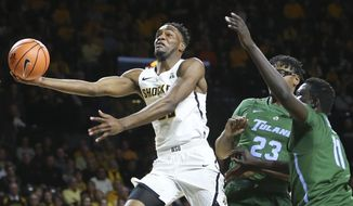 Wichita State forward Markis McDuffie goes up for a shot against Tulane forward Blake Paul, middle, and forward Bul Ajang during the first half of an NCAA college basketball game Wednesday, Feb. 21, 2018, in Wichita, Kan. (Travis Heying/The Wichita Eagle via AP)