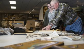 "This photo taken Jan. 31, 2018, shows Greg Bennick with Rockpile Museum's collections assistant Cara Reeves looking at photos his father Jack Bennick, took during World War II as they choose items to go into the new exhibit ""Views of Vanuata: WWII Through the Lens of Jack Bennick""  in Gillette, Wy.  (Kelly Wenzel/Gillette News Record via AP)"